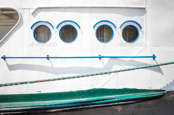 Close up picture of an old ship side and portholes