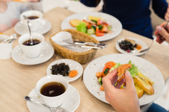 Close Up Of Family Sitting At Table Enjoying Meal - Stock Photo - Images
