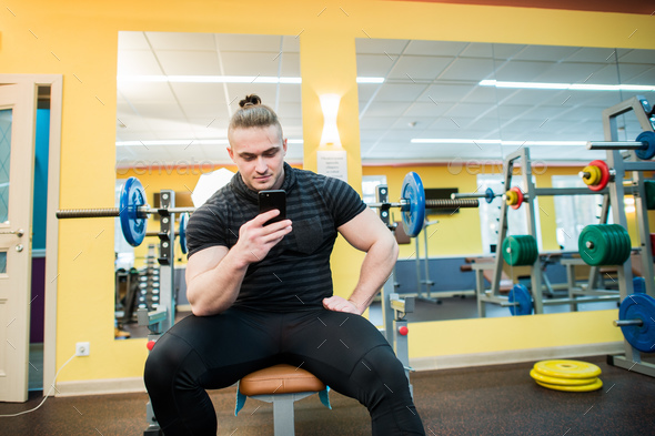 Handsome guy text messaging on his smartphone at gym. - Stock Photo - Images