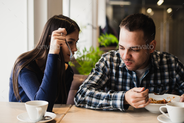 Funny couple eating noodles in cafe. He don't want to share his food with girlfriend - Stock Photo - Images