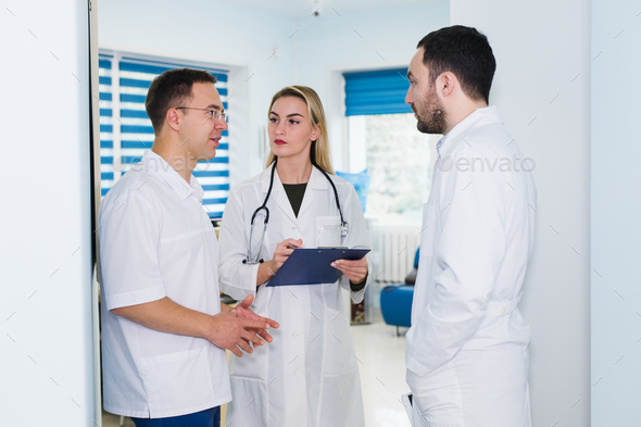 high angle view of three doctors in white coats having conversation at hospital hall - Stock Photo - Images