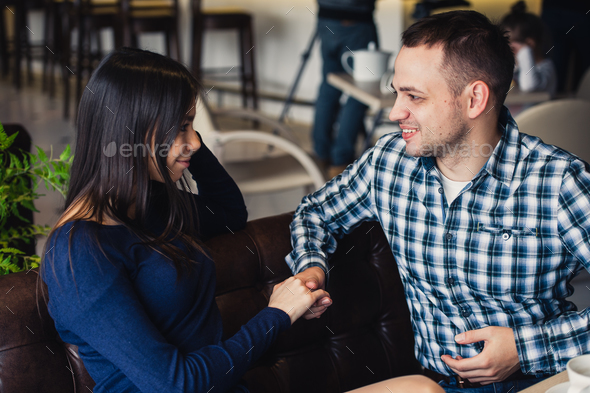 Man kissing his girlfriend's hand before dinner - Stock Photo - Images