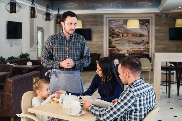 restaurant and holiday concept - waiter giving menu to happy family at cafe - Stock Photo - Images