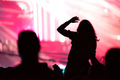 Rear view of a silhouette of a woman at concert. Bright red stage lights in the background