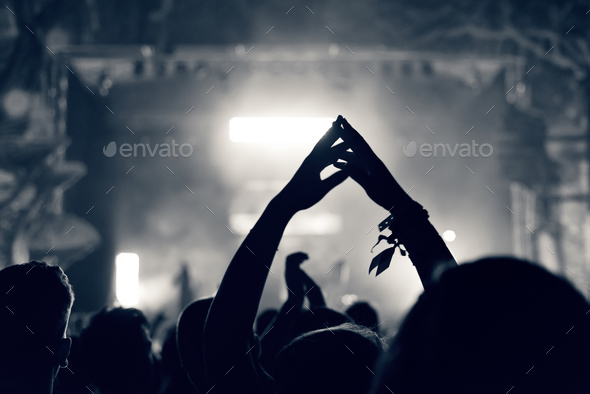 Crowd at a music concert with raising hands up, toned image