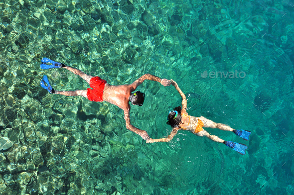 Young couple snorkeling in clear tropical water over coral reef. Above view - Stock Photo - Images