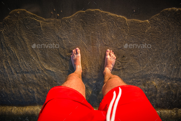 Man's feet in the sand, sea waves approaching beach