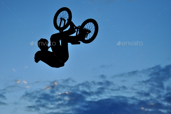 Silhouette of a BMX bycicle rider in the air