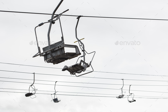 Empty chairlift with cloudy sky in the background - Stock Photo - Images