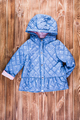 Baby blue warm jacket on wooden background