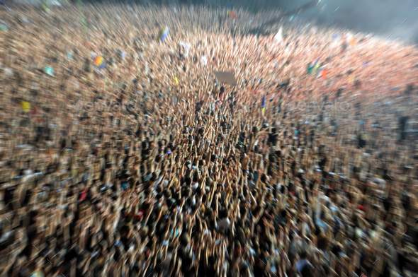 Blurred crowd partying at a music festival. Zoom in effect