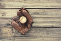 Old Baseball Mitt and Ball on Rough Wood