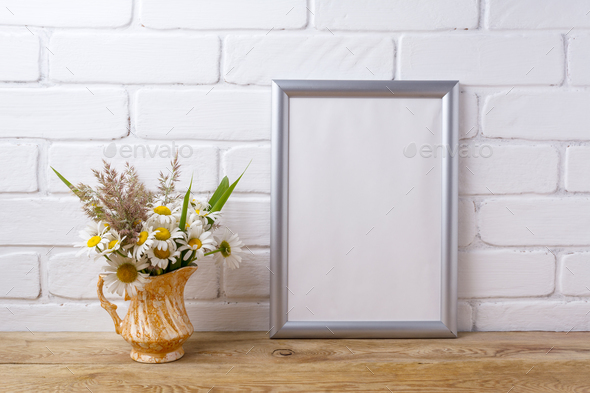 Silver frame mockup with chamomile and grass in golden pitcher - Stock Photo - Images