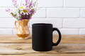 Black coffee mug mockup with chamomile and purple flowers in gol