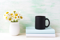 Black coffee mug mockup with white field chamomile bouquet in ha - PhotoDune Item for Sale