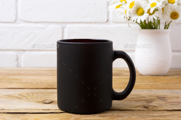 Black coffee mug mockup with chamomile bouquet in rustic vase