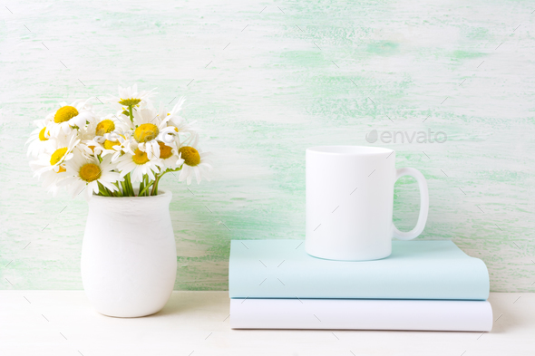 White coffee mug mockup with white field chamomile bouquet in ha