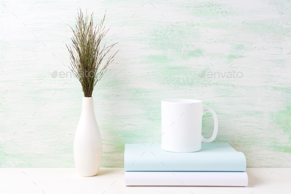 White coffee mug mockup with dark meadow grass in vase and books