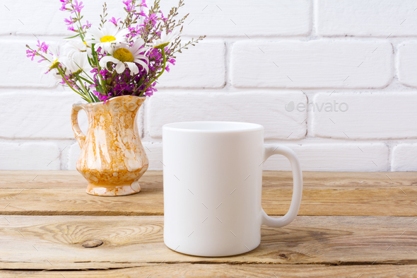 White coffee mug mockup with chamomile and purple flowers in gol