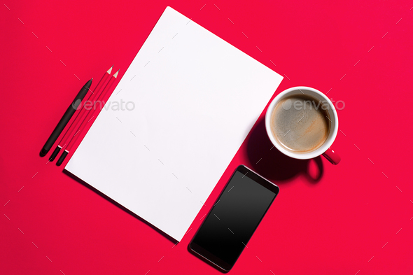Modern red office desk table with smartphone and cup of coffee.