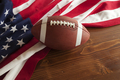 Football and American Flag on Wood Surface