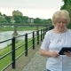 Elderly Woman Walks Along the Waterfront and Using Tablet Computer. River in the Background. - VideoHive Item for Sale