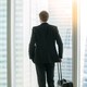 Businessman standing with suitcase near the window - PhotoDune Item for Sale