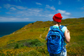 Woman with a backpack goes on a picturesque hilly terrain to the