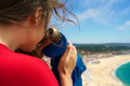 Beautiful woman using coin paid binoculars on high hill and look
