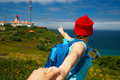 Follow me - happy young woman in a red hat and with a backpack b