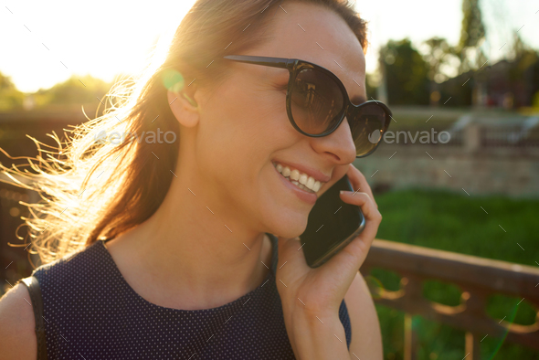 Woman in sunglasses talking on the smartphone while walking down