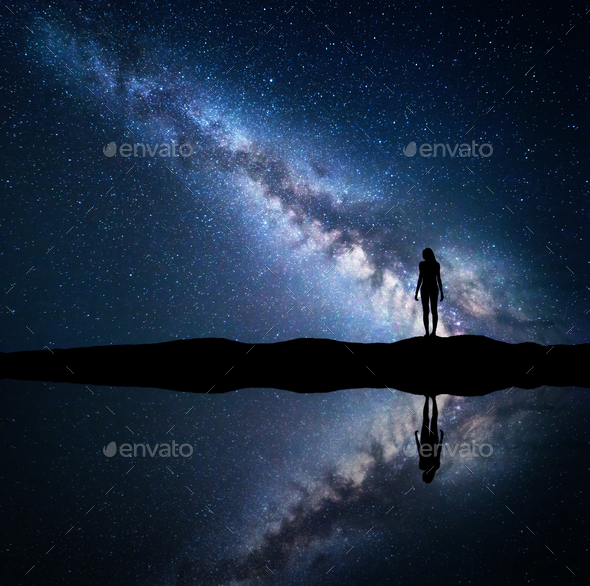 Milky Way and silhouette of a standing woman on mountain