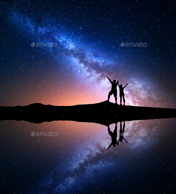 Milky Way and silhouette of happy people on the mountain