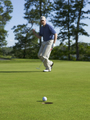 Golfer Celebrates Making a Puttt with Focus on Ball and Hole