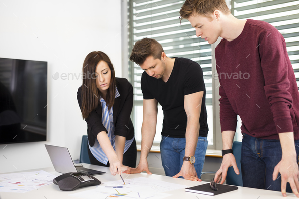 Businesswoman Explaining Plan To Male Colleagues At Desk - Stock Photo - Images