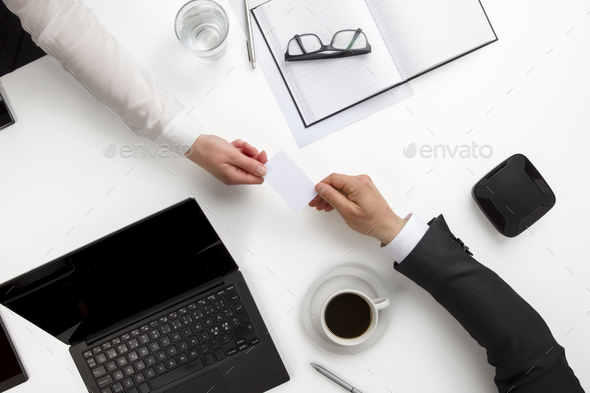 Business Colleagues Exchanging Visiting Card At Office Desk - Stock Photo - Images