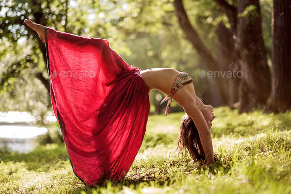 Fit young beautiful woman wearing red skirt working out outdoors in park on summer day - Stock Photo - Images