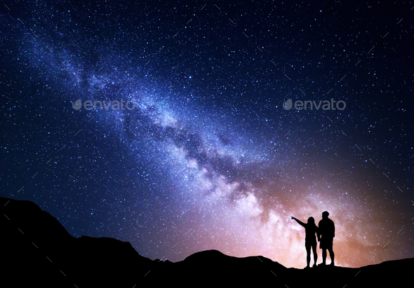 Milky Way with silhouette of people on the mountain