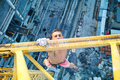 Urban climbing: rock climber hanging on jib of construction cran