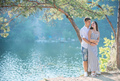 Romantic young couple standing on cliff over river