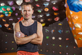 Cheerful rock climber in indoor climbing gym