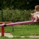 Happy Female Child in White Skirt and Shirt Playing on the Seesaw Outside During Summer Sunny Day - VideoHive Item for Sale