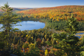 Blue Lake Surrounded by Hills with Trees in Autumn Color