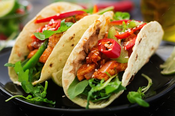 Mexican tacos with chicken fillet in tomato sauce and salsa of paprika and arugula
