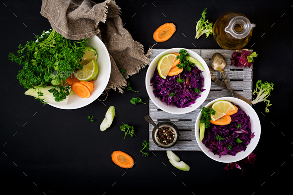 Stewed red cabbage with carrots and celery in a white bowl on a black background. Flat lay. Top view