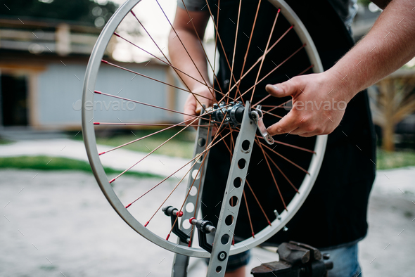 Male person adjusts bike spokes and wheel - Stock Photo - Images