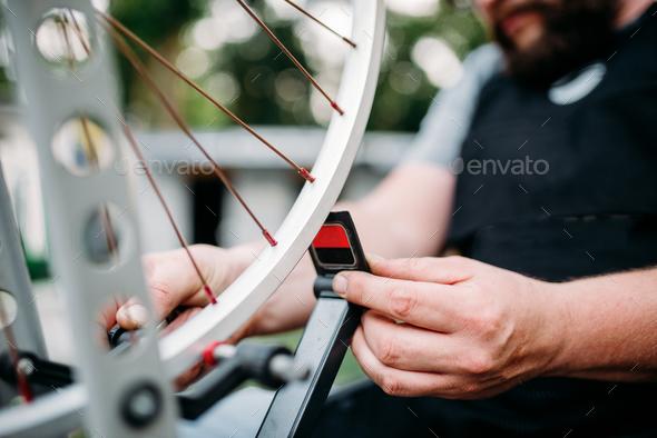 Bicycle mechanic hands repair wheel closeup - Stock Photo - Images