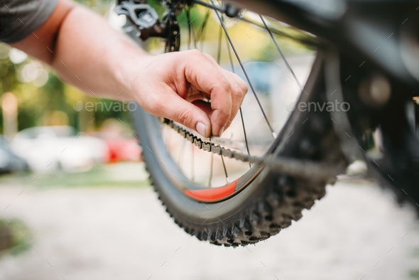 Bicycle mechanic in apron adjusts bike chain - Stock Photo - Images