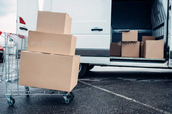 Trolley with cardboard boxes against mail van - Stock Photo - Images