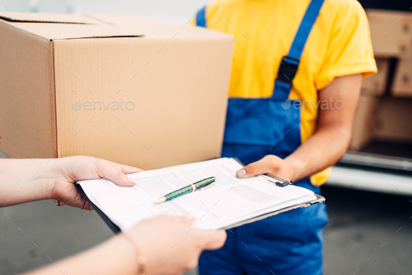Male worker in uniform gives parcel to the client - Stock Photo - Images